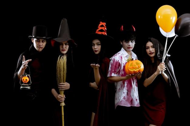 스튜디오에서 할로윈 패션 축제에 대한 개념과 검은 배경에 의상 할로윈 파티에서 젊은 아시아 그룹. 코스프레 할로윈에서 십대 아시아의 갱. 그룹 틴 타이의 의상 귀신, 악마.