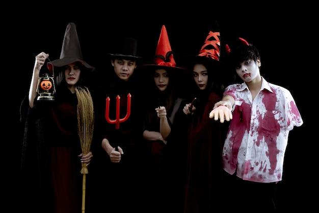 Группа молодых азиатских в костюме хэллоуин на черной стене с концепцией для фестиваля моды хэллоуина .. призрак костюма, зло группы подростков тайский.