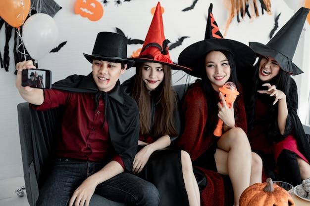 Группа молодых азиаток в костюмах ведьм, волшебников празднует вечеринку и селфи в комнате с тематикой хэллоуина. банда тайских подростков празднует вечеринку в честь хэллоуина с улыбкой. концепция партии хэллоуин дома.