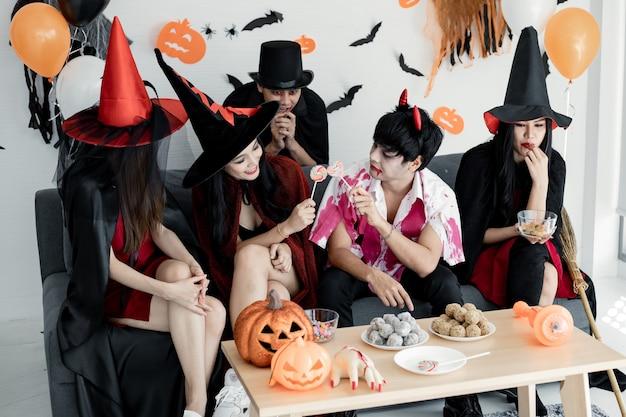 Группа молодых азиаток в костюме ведьмы, волшебника, адского празднует вечеринку в комнате на тему хэллоуина дома. банда тайских подростков празднует вечеринку в честь хэллоуина с улыбкой. концепция партии хэллоуин дома.