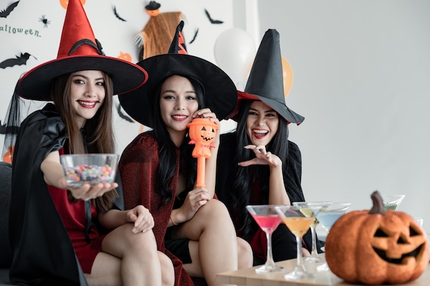 Group young asian women in costume witch celebrate party in the room for theme halloween at home. gang teen thai with celebrate halloween party with smile. concept of party halloween at home.