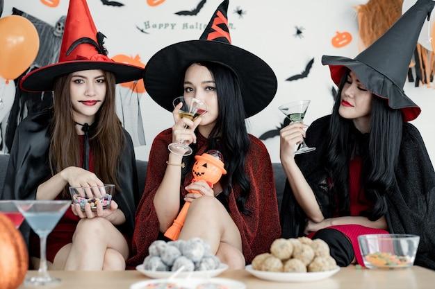 Группа молодых азиатских женщин в костюме ведьмы празднует вечеринку в комнате на тему хэллоуина дома. банда тайских подростков празднует вечеринку в честь хэллоуина с улыбкой. концепция партии хэллоуин дома.