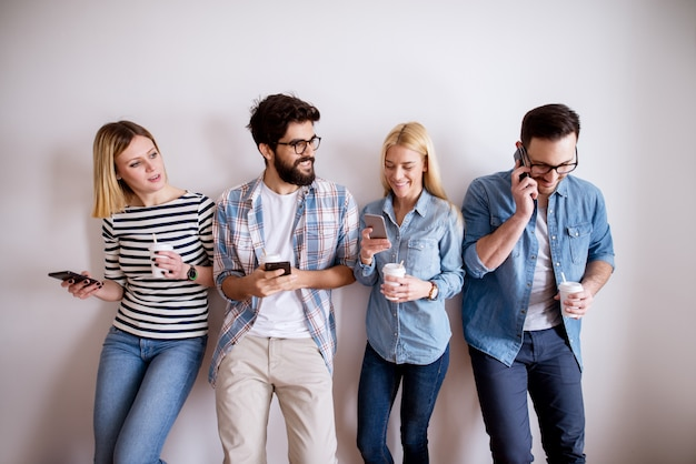 Group of young attractive colleague people standing against the wall checking mobiles and drinking coffee in paper cups for a break.