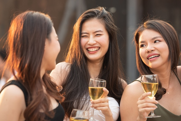 Group of young beautiful happy asian women holding glass of wine chat together with friends while celebrating dance party on outdoor rooftop nightclub,leisure lifestyle of young friendship concept.