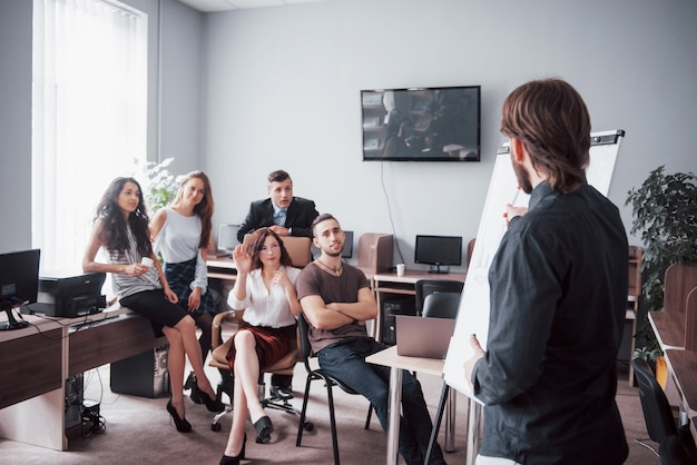Group of young business people working and communicating together in creative office.
