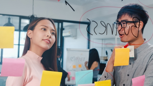 Gruppo di giovani uomini d'affari e donne d'affari che fanno brainstorming di idee che lavorano insieme condividendo dati