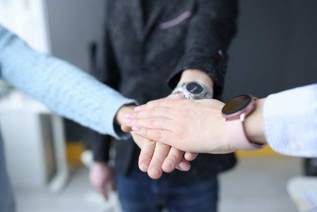 Group of young businesspeople folding their hands together closeup