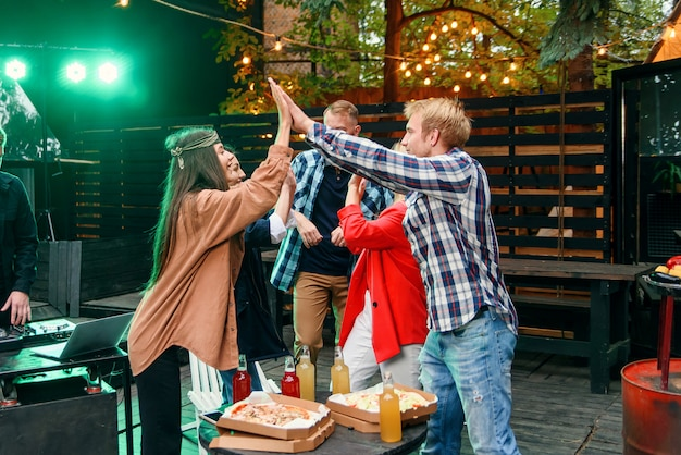 Group of young caucasian friends giving high five together and celebrating party in house courtyard at the evening.