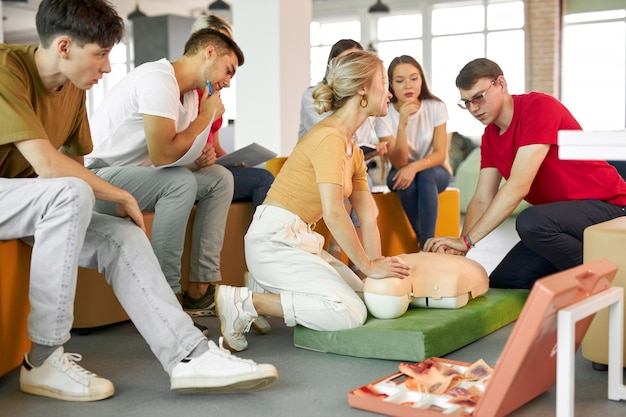 Group of young caucasian people learning how to safe a life sitting together
