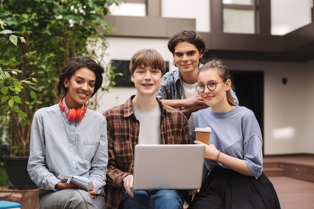 Group of young cheerful students sitting on bench and working on laptop together while happily