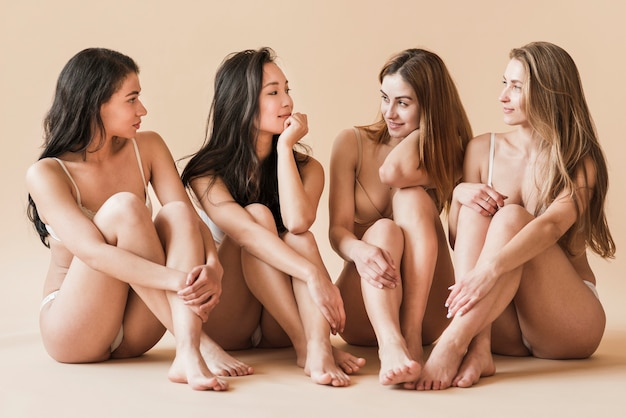 Group of young cheerful women in underwear sitting on floor