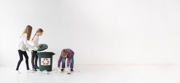 Group of young children recycling together