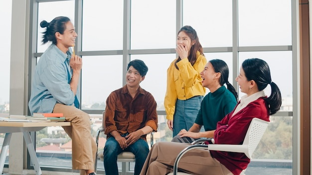 Group of young college students in smart casual wear on campus. friends brainstorming meeting talking and discussing work ideas new design project in modern office. coworker teamwork, startup concept.