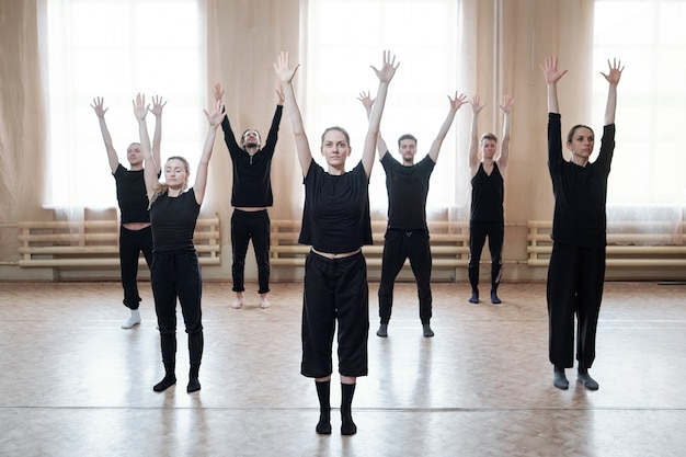 Group of young dancers in black activewear raising arms while standing on the floor against window in modern dance studio