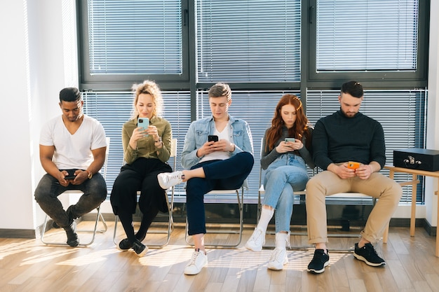 Group of young diverse ethnicity candidates using mobile phones while waiting job interview in modern office lobby. front view of multiethnic people for vacancy sitting on chairs in queue corridor.