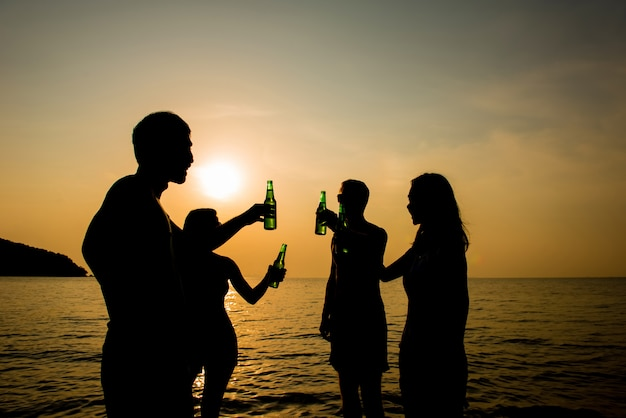 Group of young friends drinking and having party at the beach in evening sunset