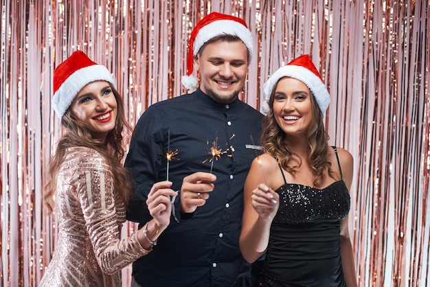 Group of young friends enjoying new year celebration with sparkles in hands.