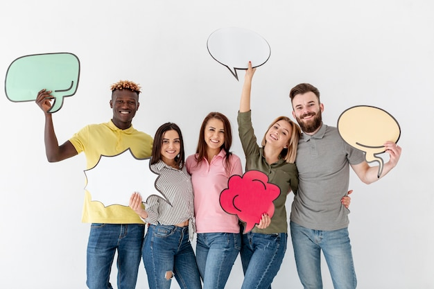 Group of young friends holding chat bubble