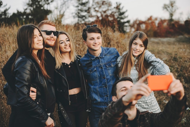 Group of young friends hugging and smiling while taking selfie.