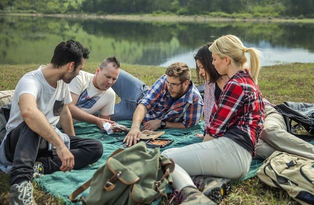 Gruppo di giovani amici seduti sull'erba vicino al lago in una giornata di sole