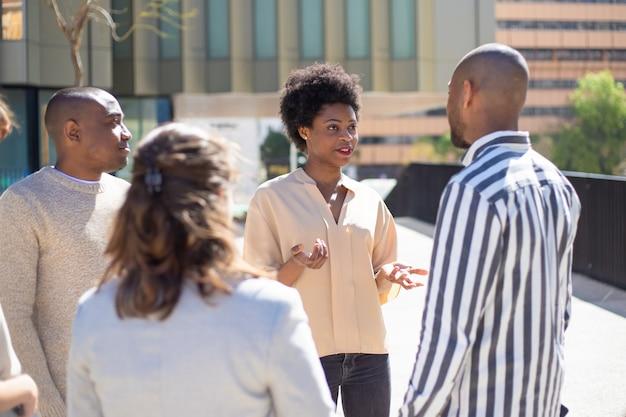 Gruppo di giovani amici in piedi sulla strada e comunicare