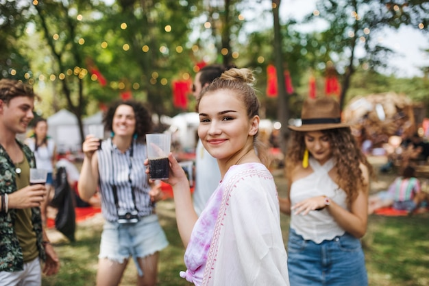 A group of young friends with drinks at summer festival, standing and talking.