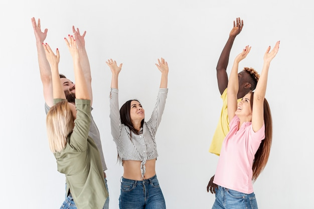 Group of young friends with hands raised above
