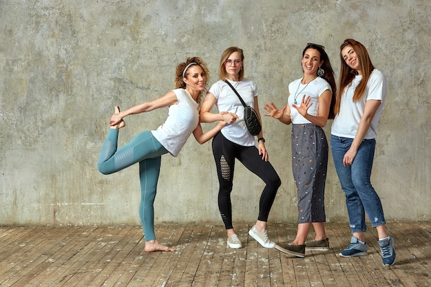 Group of young girls are posing against the wall smiling and showing gestures with their hands.