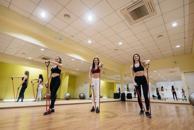 A group of young girls is engaged in fitness with an expander under the guidance of an experienced coach. fitness, healthy lifestyle.
