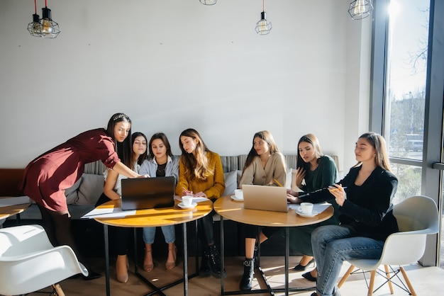 A group of young girls sit in an office at computers and discuss projects. communication and training online.