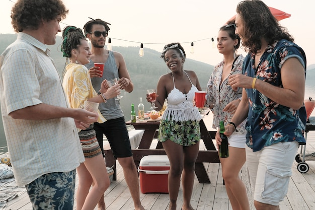 Group of young happy people dancing together and drinking alcohol during the party outdoors