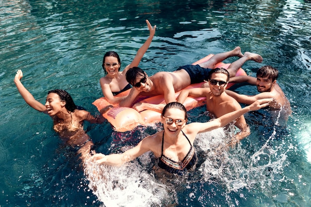 Group of young happy people having fun in pool