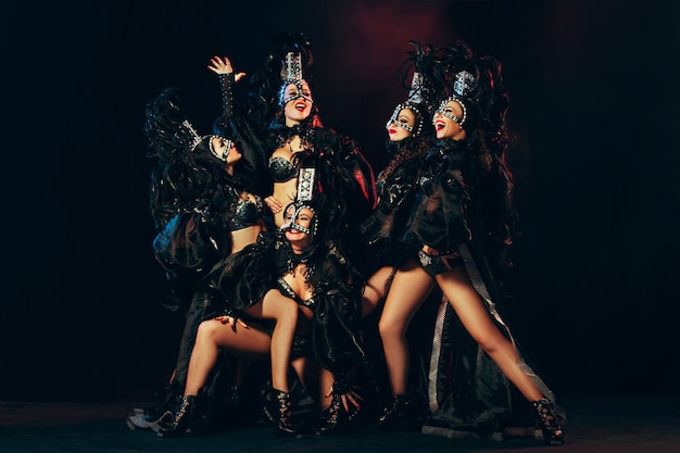 The group of young happy smiling beautiful female dancers with carnival dresses posing on black studio background