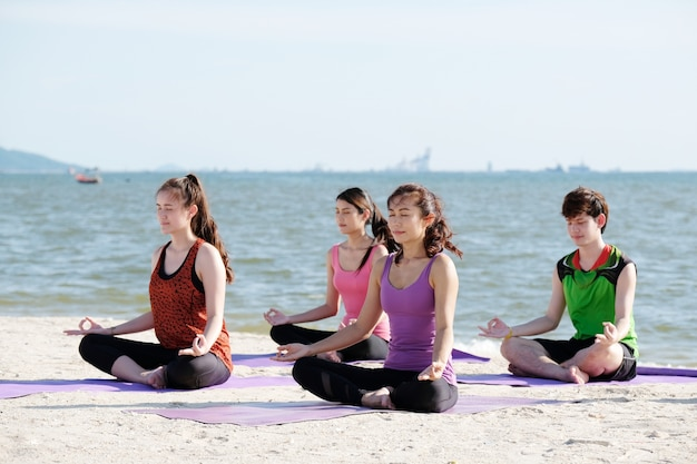 Group of young healthy asian people practicing yoga on the beach