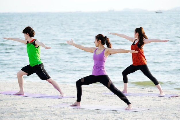Group of young healthy people practicing yoga on the beach