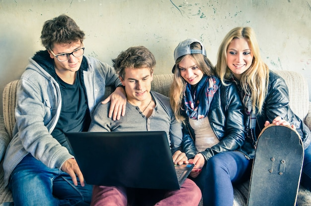 Group of young hipster best friends with computer in urban alternative studio