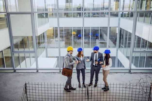 Group of young innovative highly motivated architects standing inside of building in construction process and talking about object.
