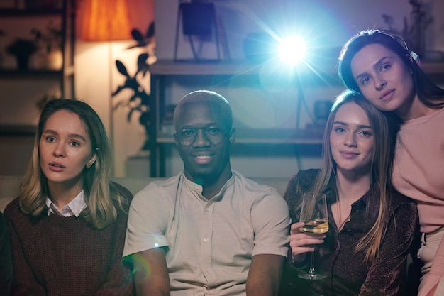 Group of young intercultural friends relaxing in living-room in front of camera and watching movie together while enjoying home party