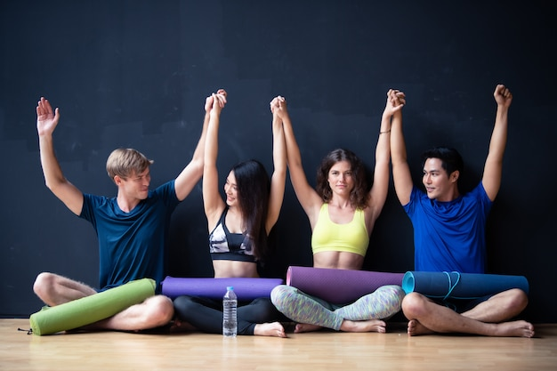 Group of young man and women sit on wall waiting for yoga class at gym