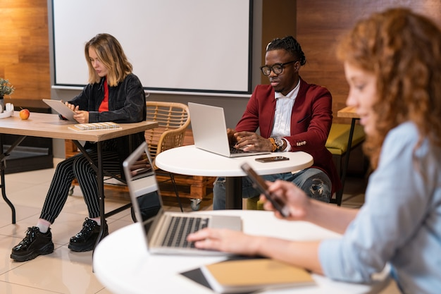 Group of young multicultural students using mobile gadgets while preparing homework in college cafe after classes