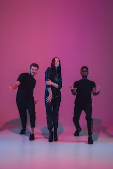 Group of young multiethnic musicians created band dancing in neon light on pink background