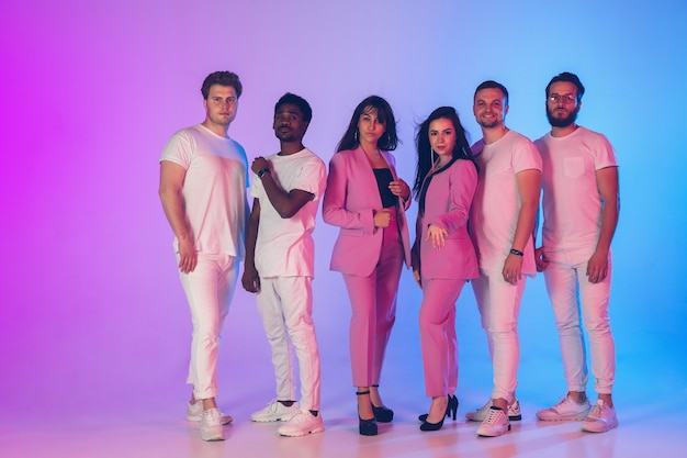 Group of young multiethnic musicians created band posing in neon light on gradient background