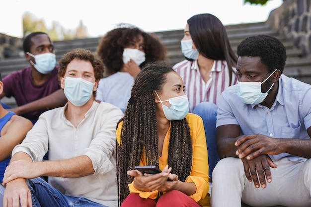 Group of young multiracial friends sitting on stairs in the city while wearing surgical face mask for coronavirus outbreak - mixed race people enjoy time together outdoor