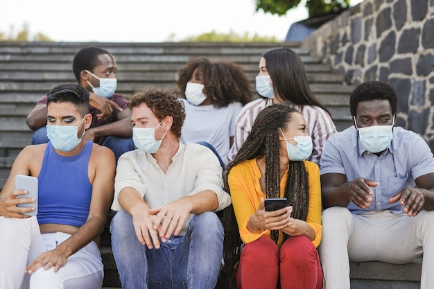 Group of young multiracial friends sitting on stairs in the city while wearing surgical face mask for coronavirus outbreak