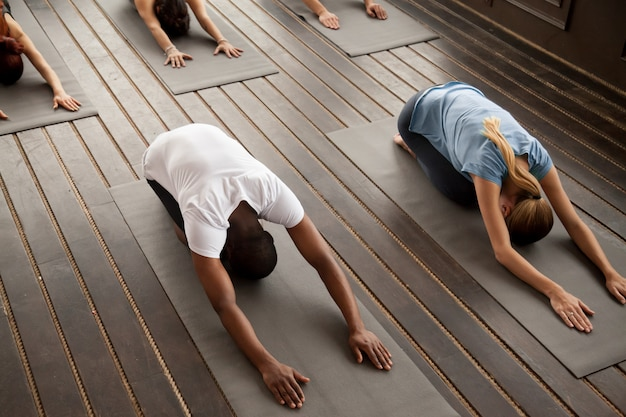 Group of young people in balasana pose, top view