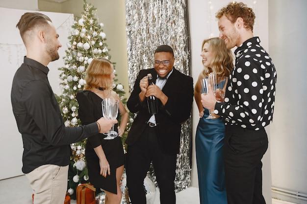 Gruppo di giovani che celebrano il nuovo anno. gli amici bevono champagne.