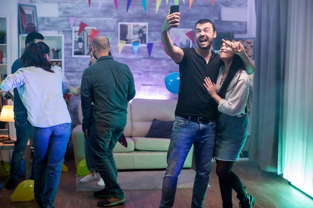 Group of young people dancing at a party while man and woman taking a selfie.