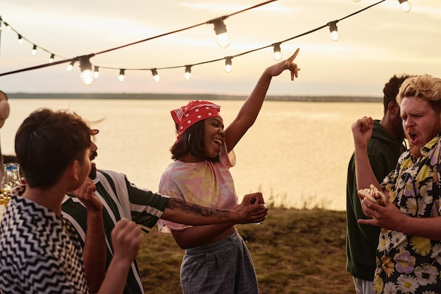 Group of young people dancing together at the party on the lakeshore during sunset