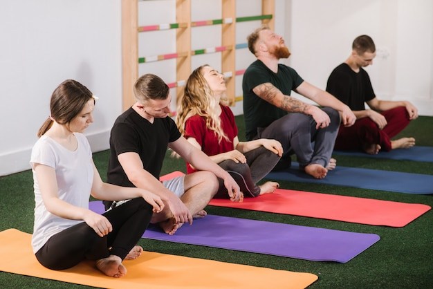 A group of a young people doing joga exercises indoors at the gym