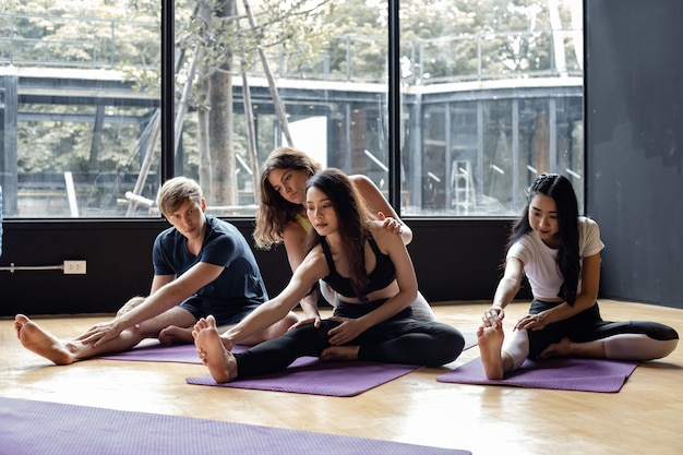 Group of young people doing yoga on a yoga mat with a trainer gradually teaching in exercise room. young women, man and their teacher practicing yoga in gym. concept of exercise with yoga.